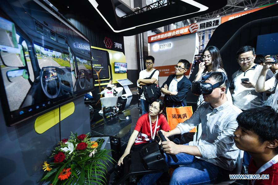 A visitor experiences virtual reality driving during the 2018 China international big data industry expo in Guiyang, Southwest China\'s Guizhou province, May 26, 2018. (Photo/Xinhua)