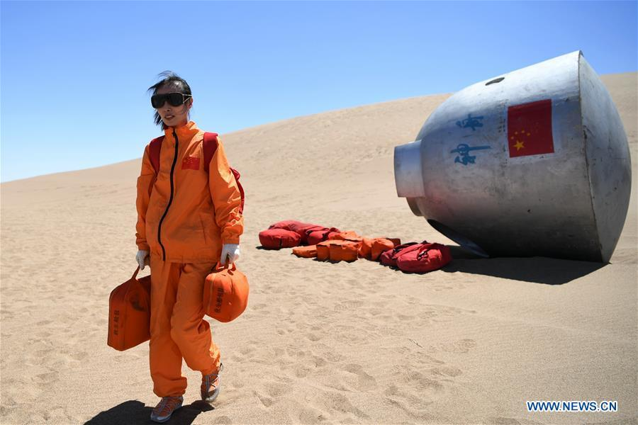 Taikonaut Wang Yaping participates in a wilderness survival training in the Badain Jaran Desert in northwest China\'s Gansu Province, May 22, 2018. Fifteen Chinese taikonauts have just completed desert survival training deep in the Badain Jaran Desert near Jiuquan Satellite Launch Center in northwest China. Organized by the Astronaut Center of China (ACC), the program was designed to prepare taikonauts with the capacity to survive in the wilderness in the event their re-entry capsule lands off target. (Xinhua/Chen Bin)