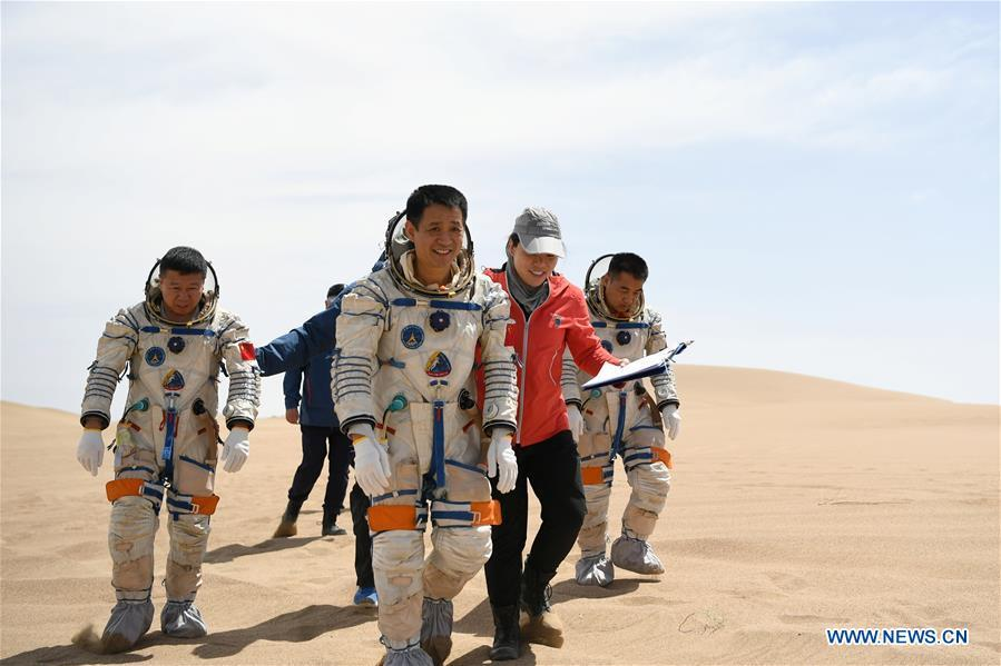Taikonauts Nie Haisheng (3rd R), Liu Wang (1st L) and Zhang Xiaoguang (1st R) participate in a wilderness survival training in the Badain Jaran Desert in northwest China\'s Gansu Province, May 17, 2018. Fifteen Chinese taikonauts have just completed desert survival training deep in the Badain Jaran Desert near Jiuquan Satellite Launch Center in northwest China. Organized by the Astronaut Center of China (ACC), the program was designed to prepare taikonauts with the capacity to survive in the wilderness in the event their re-entry capsule lands off target. (Xinhua/Chen Bin)