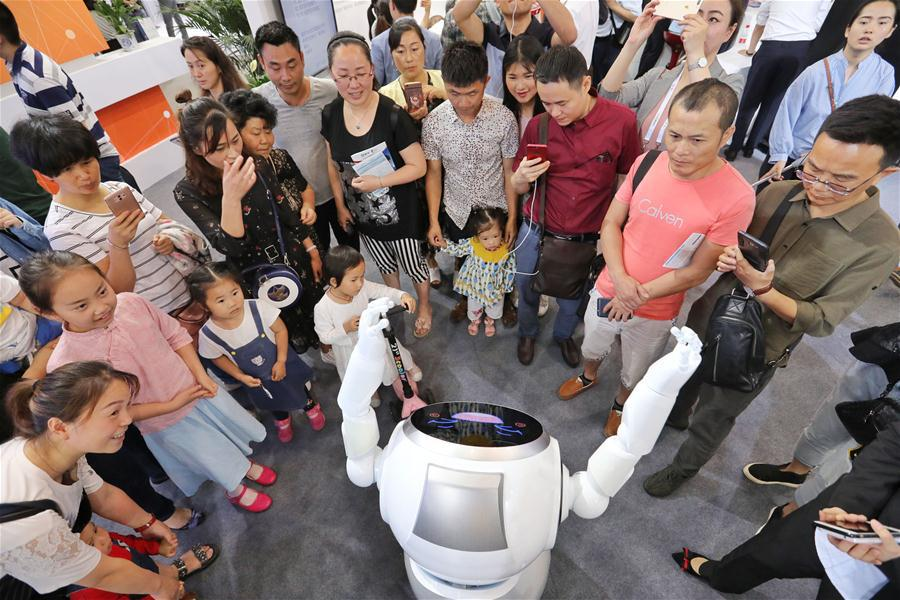 Visitors watch robot dancing during the 2018 China international big data industry expo in Guiyang, Southwest China\'s Guizhou province, May 26, 2018. (Photo/Xinhua)