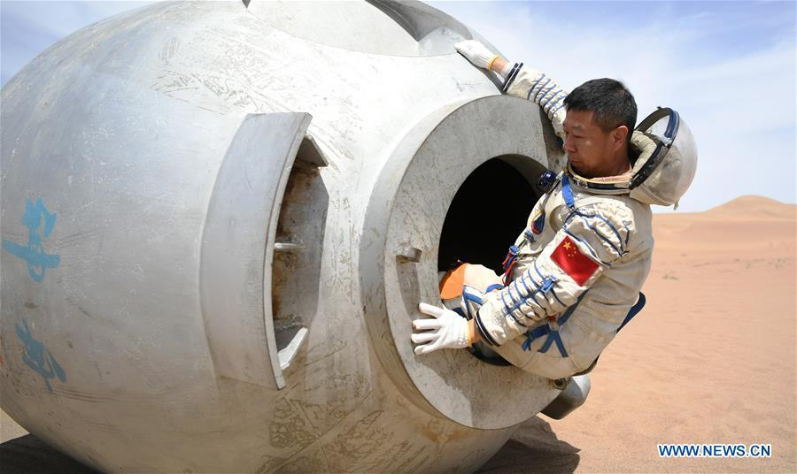 Taikonaut Liu Wang exits from a re-entry capsule during a wilderness survival training in the Badain Jaran Desert in northwest China\'s Gansu Province, May 17, 2018. Fifteen Chinese taikonauts have just completed desert survival training deep in the Badain Jaran Desert near Jiuquan Satellite Launch Center in northwest China. Organized by the Astronaut Center of China (ACC), the program was designed to prepare taikonauts with the capacity to survive in the wilderness in the event their re-entry capsule lands off target. (Xinhua/Chen Bin)