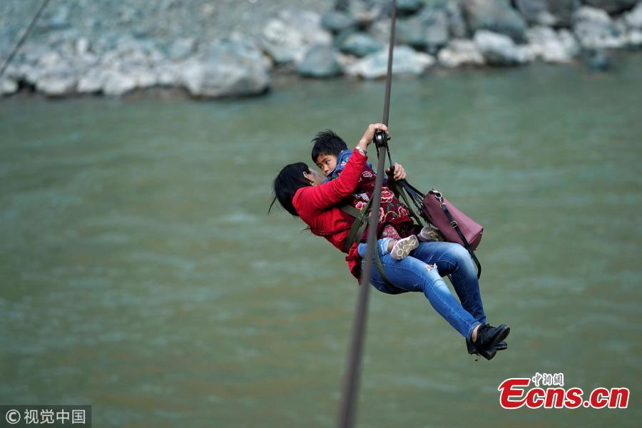 A 40-year old Lisu woman and her daughter leave a village with a zipline across the Nujiang River in Nujiang Lisu Autonomous Prefecture in Southwest China's Yunnan Province. Villagers have to use a zipline to cross the raging river. (Photo/VCG)