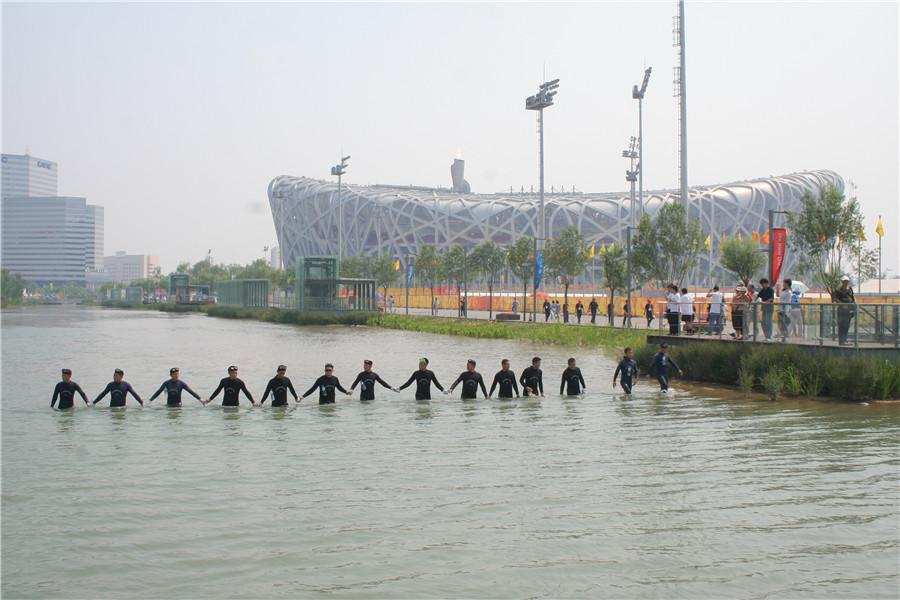 The squad\'s divers conduct security checks in the waterway beside Beijing\'s National Stadium. (Photo provided to China Daily)