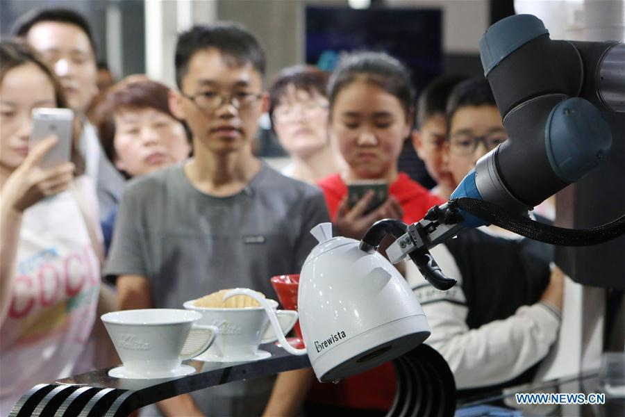 Visitors look at a coffee brewing robot during the 2018 China international big data industry expo in Guiyang, Southwest China\'s Guizhou province, May 26, 2018. The expo opened in Guiyang Saturday, attracting over 40,000 participants from nearly 30 countries. (Photo/Xinhua)