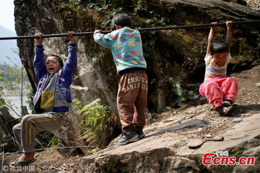 Village children play with a zipline cable in Nujiang Lisu Autonomous Prefecture in Southwest China's Yunnan Province. Villagers have to use a zipline to cross the raging river. (Photo/VCG)