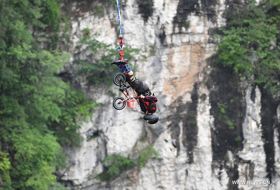 An enthusiast goes bungee jumping from Zhangjiajie Grand Canyon\'s glass-bottom bridge, during a challenge in Zhangjiajie scenic spot, central China\'s Hunan Province, May 26, 2018. Enthusiasts from Russia, Australia, Britain and other countries and regions participated in the challenge on Saturday. (Xinhua/Yan Yuan)