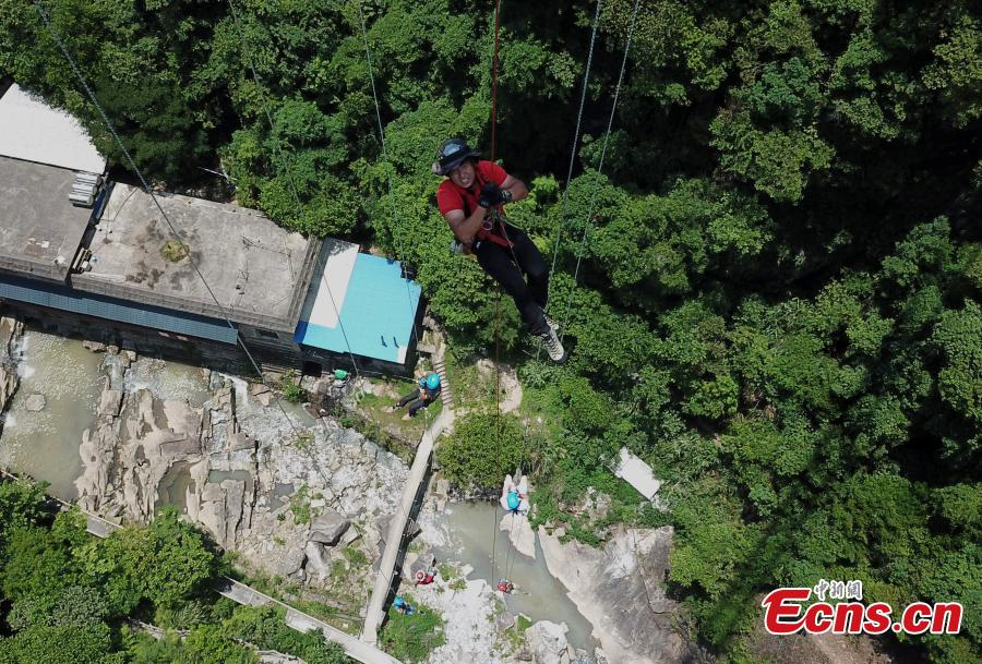 Extreme sports enthusiasts take on the challenge of descending from and then climbing back to a suspended glass bridge 188 meters above the ground at a scenic spot in Youxi County, East China's Fujian Province, May 26, 2018. More than 20 participants fast-roped down and then climbed back up from under the bottom of the bridge. (Photo: China News Service/Wang Dongming)