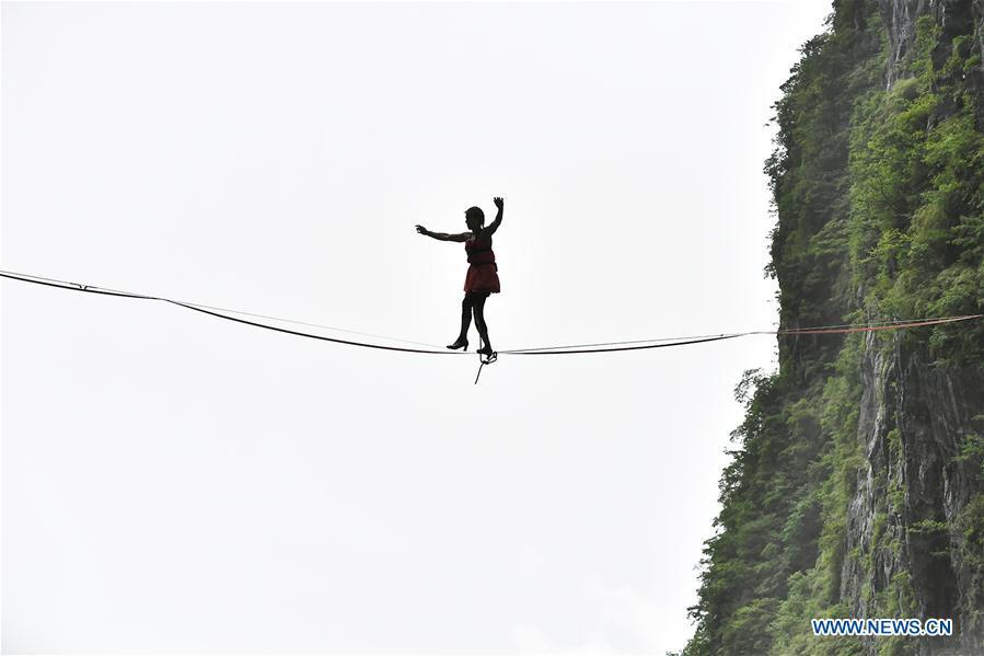 Mimi Guesdon of France participates in a slackline contest in high heels in Zhangjiajie, central China\'s Hunan Province, May 27, 2018. (Xinhua/Shao Ying)