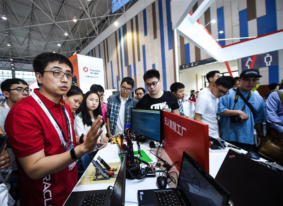An engineer introduces an unmanned intelligent factory during the 2018 China international big data industry expo in Guiyang, Southwest China\'s Guizhou province, May 26, 2018. (Photo/Xinhua)