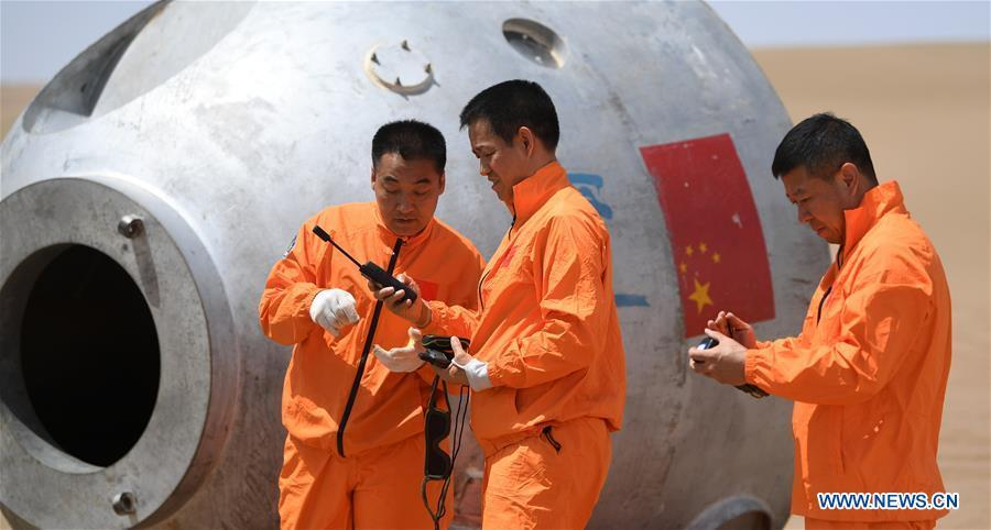 Taikonauts Nie Haisheng (C), Zhang Xiaoguang (L) and Liu Wang participate in a wilderness survival training in the Badain Jaran Desert in northwest China\'s Gansu Province, May 17, 2018. Fifteen Chinese taikonauts have just completed desert survival training deep in the Badain Jaran Desert near Jiuquan Satellite Launch Center in northwest China. Organized by the Astronaut Center of China (ACC), the program was designed to prepare taikonauts with the capacity to survive in the wilderness in the event their re-entry capsule lands off target. (Xinhua/Chen Bin)