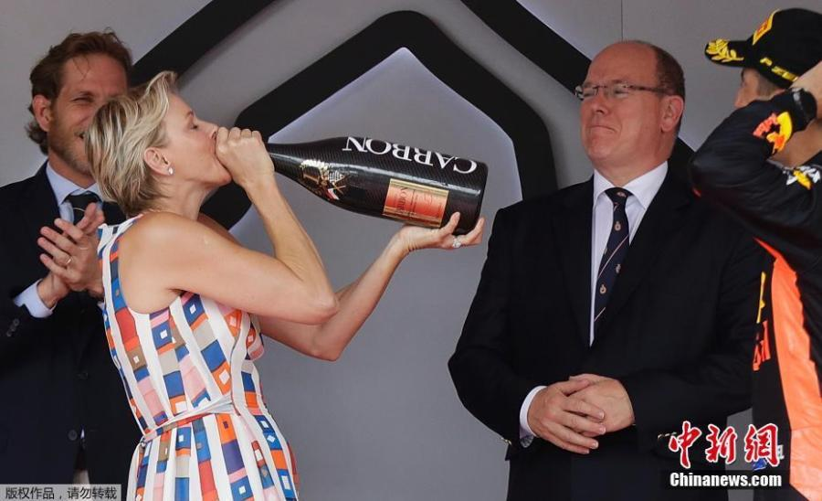 Princess Charlene of Monaco drinks the winner\'s champagne from the bottle as Daniel Ricciardo cheers her on in Monte Carlo, Monaco, May 27, 2018. (Photo/Agencies)