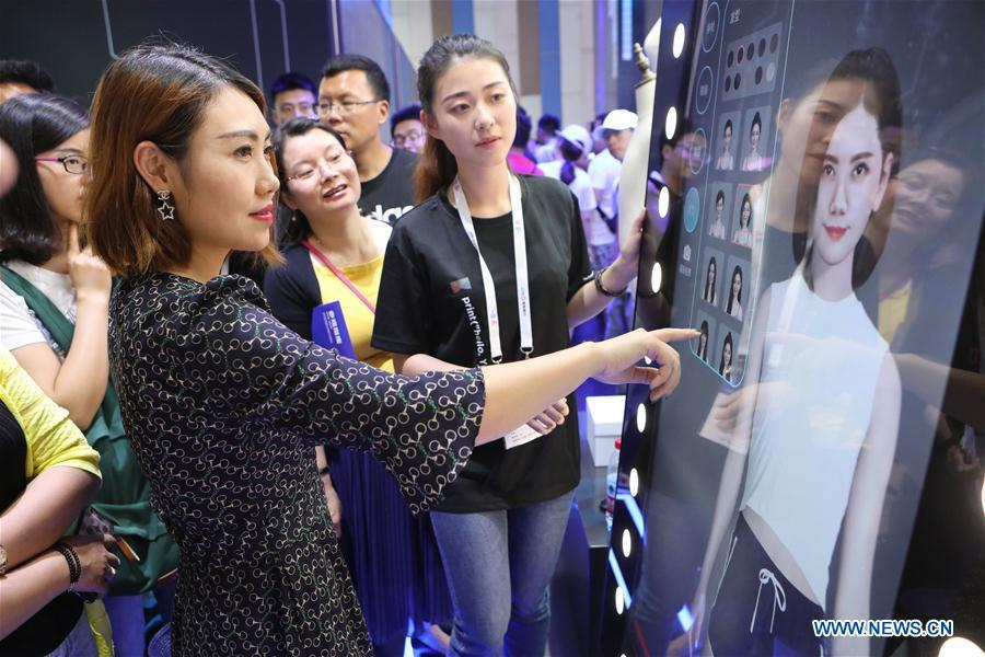 A visitor experiences a virtual fitting equipment of Alibaba during the 2018 China international big data industry expo in Guiyang, Southwest China\'s Guizhou province, May 26, 2018.(Photo/Xinhua)