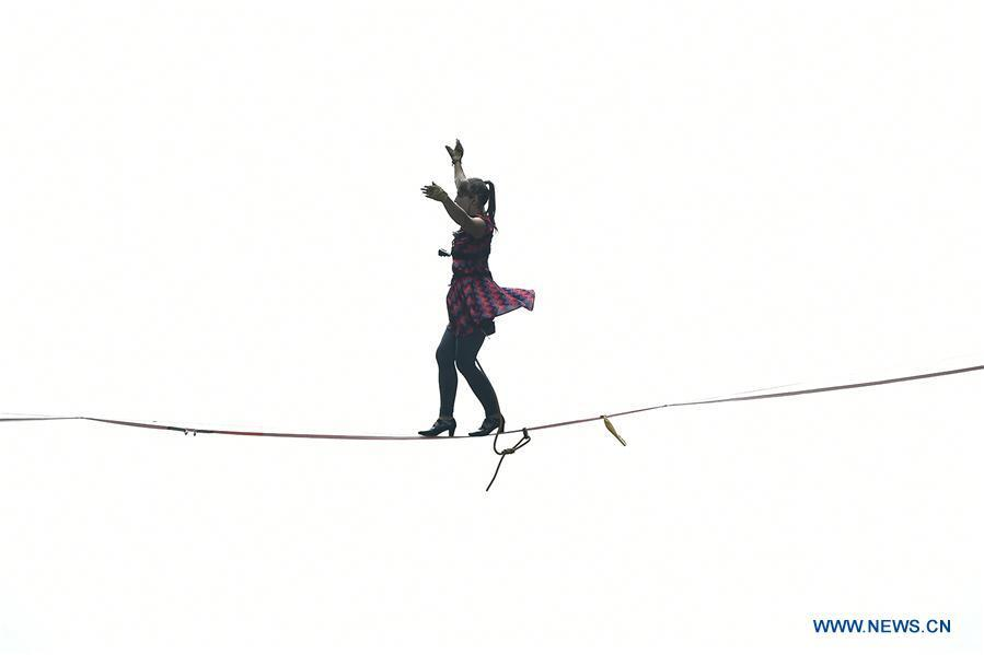Faith Dickey of the U.S. participates in a slackline contest in high heels in Zhangjiajie, central China\'s Hunan Province, May 27, 2018. (Xinhua/Shao Ying)