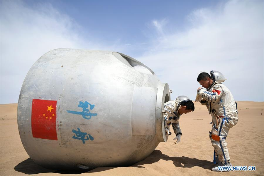 Taikonauts Nie Haisheng (L) and Liu Wang exit from a re-entry capsule during a wilderness survival training in the Badain Jaran Desert in northwest China\'s Gansu Province, May 17, 2018. Fifteen Chinese taikonauts have just completed desert survival training deep in the Badain Jaran Desert near Jiuquan Satellite Launch Center in northwest China. Organized by the Astronaut Center of China (ACC), the program was designed to prepare taikonauts with the capacity to survive in the wilderness in the event their re-entry capsule lands off target. (Xinhua/Chen Bin)