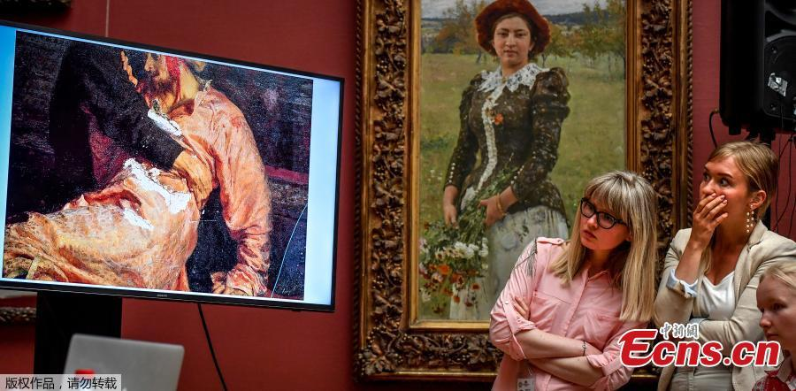 Two journalists look at the screen showing the damaged world famous painting of the 16th century Russian Tsar, titled \'Ivan the Terrible and his Son Ivan on November 16, 1581.\' by Ilya Repin during a press conference at the Russian State Tretyakov Gallery in Moscow on May 28, 2018. Russian police on Saturday said they arrested a man for vandalising one of the best known works of 19th century painter Ilya Repin, depicting Ivan the Terrible killing his son, at a gallery in Moscow. (Photo/Agencies)