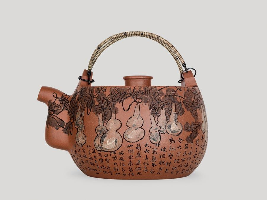 Artist Huang Yongyu is known for his great vigor and versatility. He paints, writes, designs, creates prints and draws comics. And at 94, he has fallen into a new habit of art creation: carving figures on earthen zisha teapots. (Photo provided to China Daily)