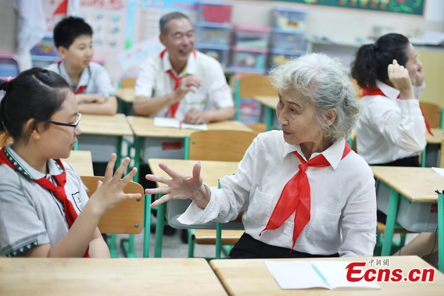 Photo taken on May 28, 2018 shows five elderly people, 73 years old on average, put on white shirts and red scarfs to pose for an awareness event in the run up to Children's Day at an elementary school in Nanjing, East China's Jiangsu Province. Organizer said the event aimed to inspire more people to take care of elderly people. (Photo: China News Service/Yang Bo)