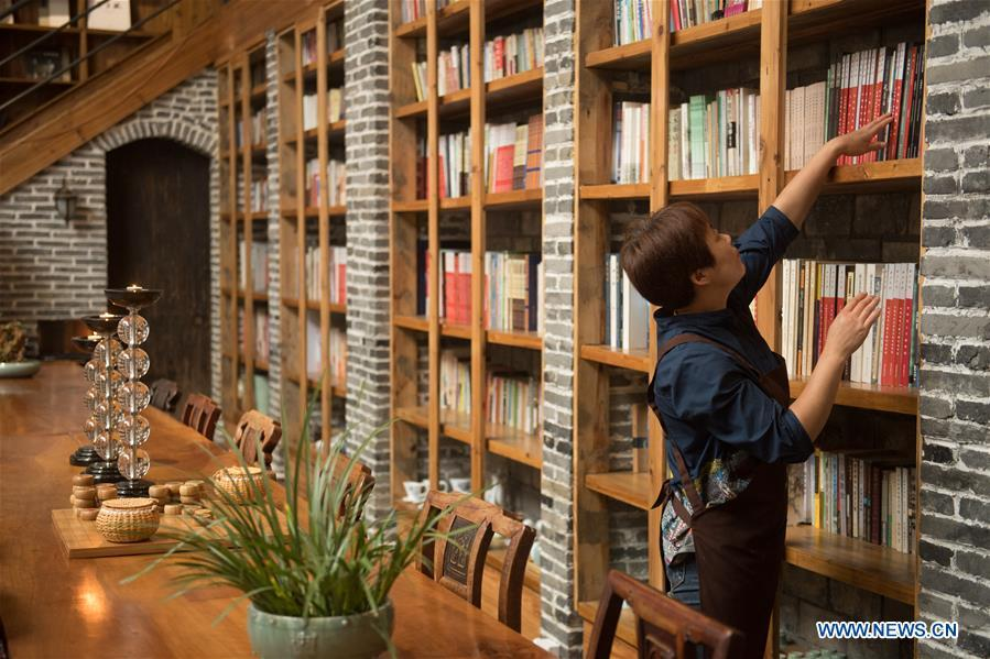 Villager Yao Wenzhen arranges books at the library in a hostel in Moganshan Town in Deqing County, east China\'s Zhejiang Province, May 29, 2018. The owner of the hostel Zhu Jindong, who worked in publishing, founded the hostel in 2015. The library collecting about 20,000 books in the hostel made it famous and attracted many tourists. (Xinhua/Weng Xinyang)