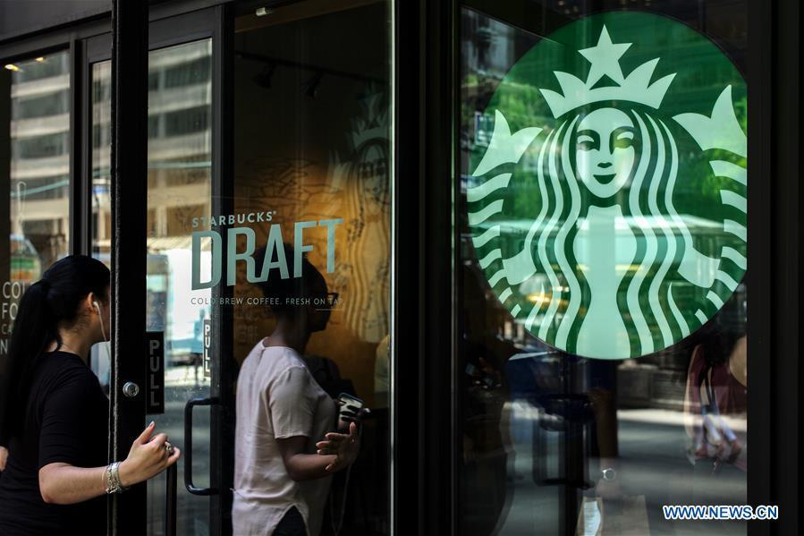 People walk into a Starbucks store in Manhattan, New York, the United States, May 29, 2018. Starbucks closed about 8,000 company-owned stores in the United States on Tuesday afternoon to offer nearly 175,000 employees a mandatory anti-bias training. (Xinhua/Li Muzi)