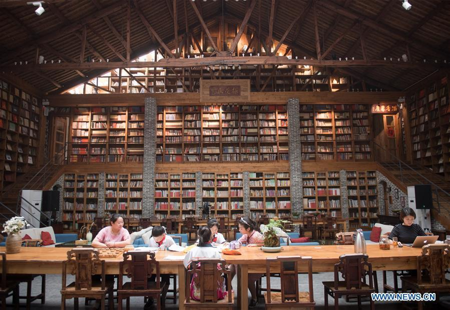 Students of Miaoqian Village study at the library in a hostel in Moganshan Town in Deqing County, east China\'s Zhejiang Province, May 29, 2018. The owner of the hostel Zhu Jindong, who worked in publishing, founded the hostel in 2015. The library collecting about 20,000 books in the hostel made it famous and attracted many tourists. (Xinhua/Weng Xinyang)