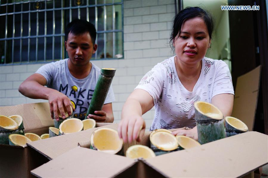 Villagers package bamboo wine at Daliu Village, Longji Town, Longsheng County, south China\'s Guangxi Zhuang Autonomous Region, May 30, 2018. Best known for its rich bamboo materials, Longji has developed bamboo wine industry in recent years. The bamboo wine, usually taking three or four months for brewing in growing bamboos, is popular here. (Xinhua/Huang Yongdan)