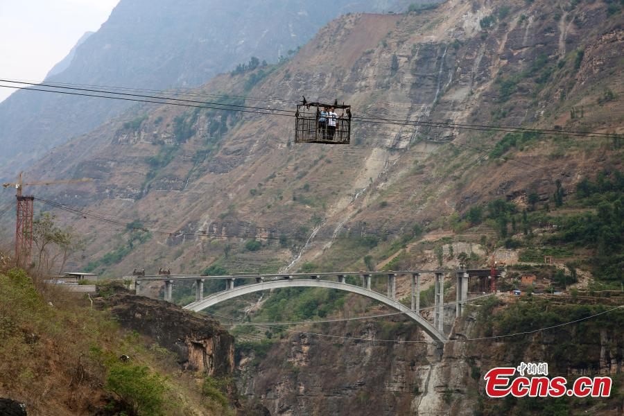 Photo taken on May 30, 2018 shows the Yingge Bridge under construction over the Jinsha River between Yingge Village in Qiaojia County, Yunnan Province and Yanjiang Village in Liangshan Prefecture, Sichuan Province. Construction of the majority of the bridge was completed Wednesday. Until now, a 470-meter cableway 260 meters above the river had served as the main transport option for villagers. It is known as the highest of its kind in Asia. In November 2015, authorities began building the bridge to improve local transport. The new bridge will be nine meters wide, 385.5 meters long, and 200 meters above the river. (Photo: China News Service/Yan Keren)