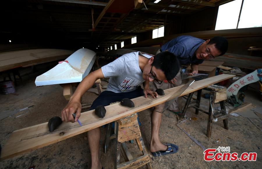 Fang Jianwei works in a dragon boat-making factory in Fangzhuang Village, Minhou County, East China's Fujian Province, May 30, 2018. The village has a 700-year history of dragon-boat making. As fewer young people work to inherit the skills of the traditional craft, the village is now home to just four factories still using ancient simple tools to make the handmade boats. Fang, 29, is the only one in his family to continue the occupation. The Dragon Boat Festival is celebrated on the fifth day of the fifth month of the Chinese lunar calendar and falls on June 18 this year. (Photo: China News Service/Wang Dongming)