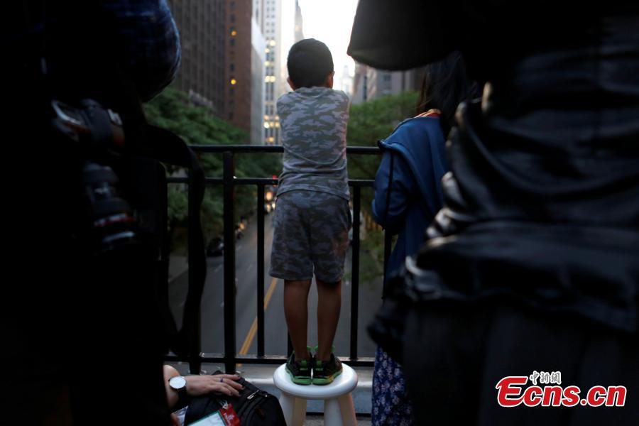 A boy stands on a footstool at Tudor City on 42nd St in Manhattan to watch the phenomenon known as Manhattanhenge in New York City, New York, U.S. May 29, 2018.(Photo/Agencies)