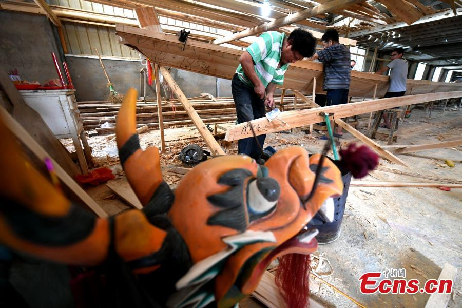 Workers make a dragon boat at a factory in Fangzhuang Village, Minhou County, East China's Fujian Province, May 30, 2018. The village has a 700-year history of dragon-boat making. As fewer young people work to inherit the skills of the traditional craft, the village is now home to just four factories still using ancient simple tools to make the handmade boats. The Dragon Boat Festival is celebrated on the fifth day of the fifth month of the Chinese lunar calendar and falls on June 18 this year. (Photo: China News Service/Wang Dongming)