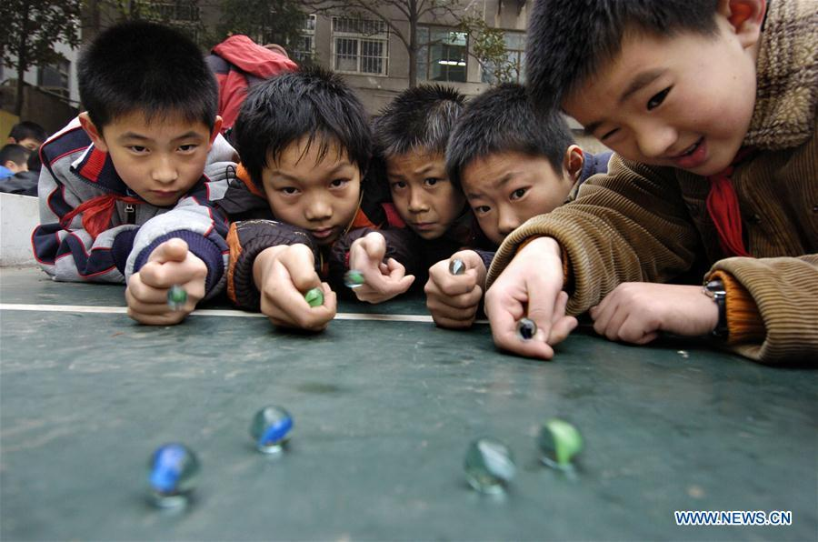In this file photo taken on Dec. 18, 2007, students play a classic marble game at Changjianglu Primary School in Nanjing, east China\'s Jiangsu Province. As China celebrates the International Children\'s Day, there arises the occasion for grown-ups to think back over the joys of childhood. With the evolution of technology and lifestyle, children are exposed to a wider range of entertainment. Nevertheless, joy would remain a childhood motif no matter how its forms change with time. (Xinhua/Sun Can)