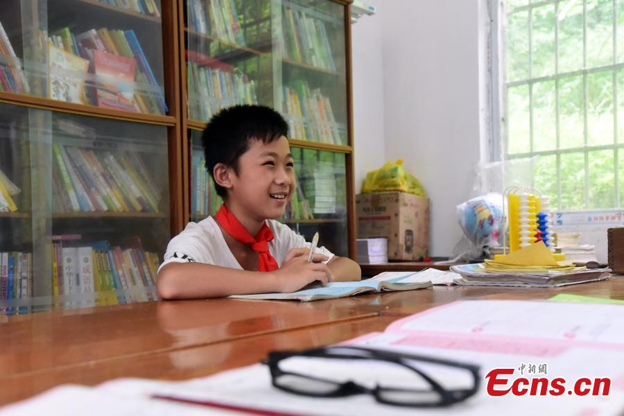 Li Jianwen, 10, learns with Pan Shanji, the only teacher at Dayadong Primary School in Liucheng County, South China's Guangxi Zhuang Autonomous Region, May 31, 2018. It takes Li about one and a half hours to climb the mountain to his school, a three-hour return commute each day. (Photo: China News Service/Wang Yizhao)
