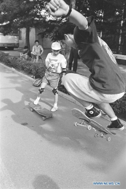 In this file photo issued on August 1, 1994, two boys practise skateboard in a square in Beijing, capital of China. As China celebrates the International Children\'s Day, there arises the occasion for grown-ups to think back over the joys of childhood. With the evolution of technology and lifestyle, children are exposed to a wider range of entertainment. Nevertheless, joy would remain a childhood motif no matter how its forms change with time. (Xinhua/Zhang Xu)