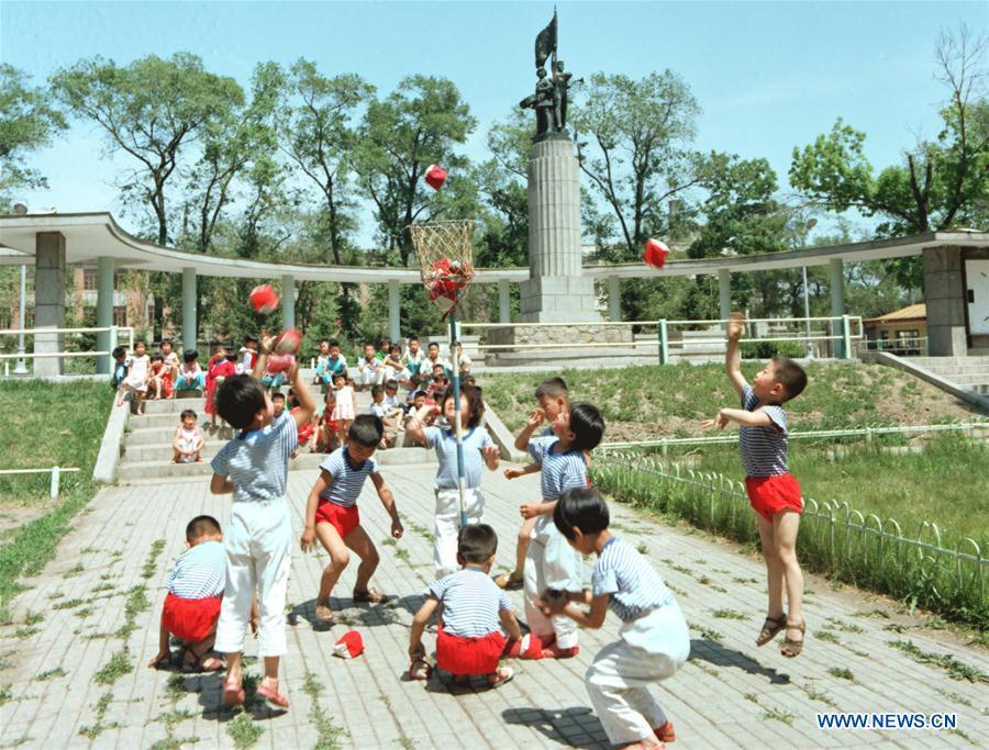 In this file photo taken in 1983, children play a bag toss game at a public park in Harbin, northeast China\'s Heilongjiang Province. As China celebrates the International Children\'s Day, there arises the occasion for grown-ups to think back over the joys of childhood. With the evolution of technology and lifestyle, children are exposed to a wider range of entertainment. Nevertheless, joy would remain a childhood motif no matter how its forms change with time. (Xinhua/Hu Wei)