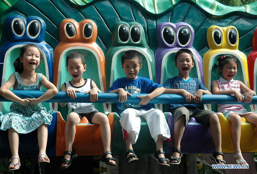 In this file photo taken on July 28, 2006, children ride a thrill machine at an amusement park in Hangzhou, east China\'s Zhejiang Province. As China celebrates the International Children\'s Day, there arises the occasion for grown-ups to think back over the joys of childhood. With the evolution of technology and lifestyle, children are exposed to a wider range of entertainment. Nevertheless, joy would remain a childhood motif no matter how its forms change with time. (Xinhua/Shao Quanda)