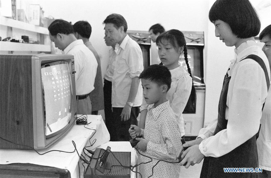 In this file photo issued on July 27, 1985, a boy tries a gaming console during a toy fair in Fuzhou, southeast China\'s Fujian Province. As China celebrates the International Children\'s Day, there arises the occasion for grown-ups to think back over the joys of childhood. With the evolution of technology and lifestyle, children are exposed to a wider range of entertainment. Nevertheless, joy would remain a childhood motif no matter how its forms change with time. (Xinhua/Huang Xingquan)