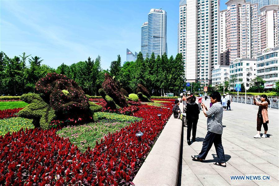 Tourists take photos at the May Fourth Square in Qingdao, east China\'s Shandong Province, May 31, 2018. The 18th Shanghai Cooperation Organization (SCO) Summit is scheduled for June 9-10 in Qingdao. (Xinhua/Guo Xulei)