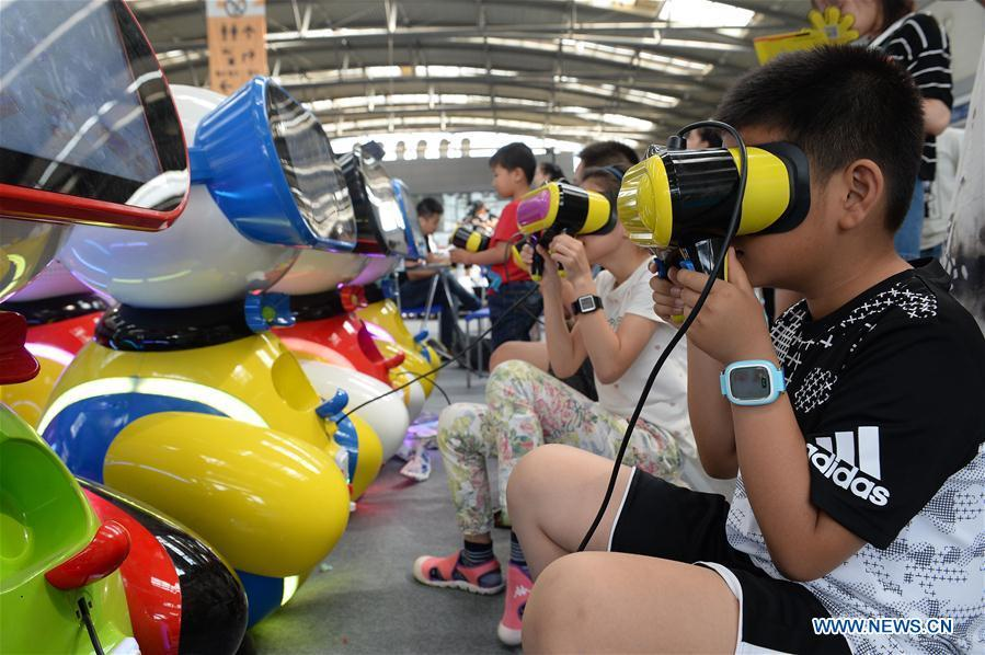 In this file photo taken on May 28, 2017, children wear VR (virtual reality) equipment during a technology event in Xi\'an, northwest China\'s Shaanxi Province. As China celebrates the International Children\'s Day, there arises the occasion for grown-ups to think back over the joys of childhood. With the evolution of technology and lifestyle, children are exposed to a wider range of entertainment. Nevertheless, joy would remain a childhood motif no matter how its forms change with time. (Xinhua/Liu Xiao)