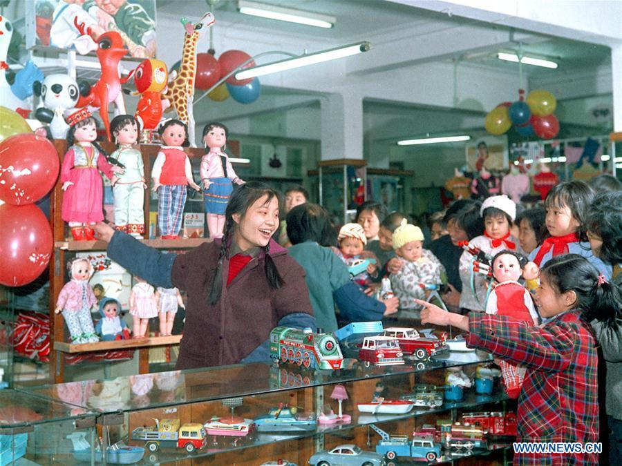 In this file photo issued on March 8, 1975, parents buy toys for their children at a shop in east China\'s Shanghai. As China celebrates the International Children\'s Day, there arises the occasion for grown-ups to think back over the joys of childhood. With the evolution of technology and lifestyle, children are exposed to a wider range of entertainment. Nevertheless, joy would remain a childhood motif no matter how its forms change with time. (Xinhua/Shen Zhengchu)