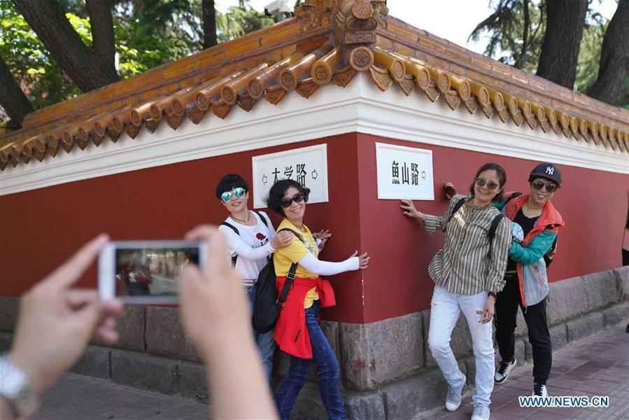 Tourists take photos at the corner of Daxue road and Yushan road in Qingdao, east China\'s Shandong Province, May 31, 2018. The 18th Shanghai Cooperation Organization (SCO) Summit is scheduled for June 9-10 in Qingdao. (Xinhua/Purbu Zhaxi)