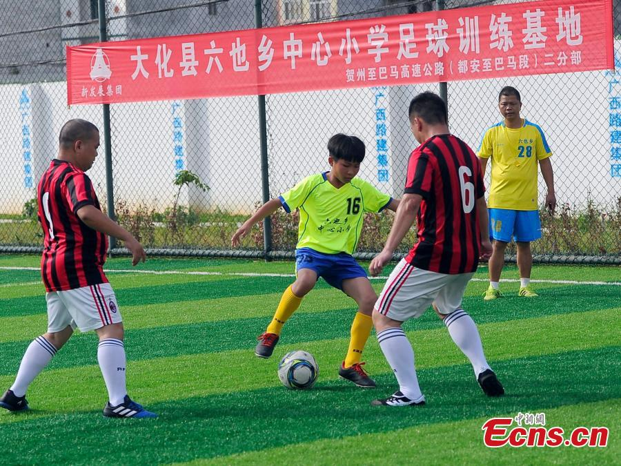 Wei Yuncheng (2ndL) plays in a football match in Liuye Township, Dahua Yao Autonomous County, South China's Guangxi Zhuang Autonomous Region. Wei, a member of the Liuye Central Elementary School boys football team, said his dream is to one day leave his mountain home to explore the outside world by playing football well. The mountainous county, with a population of 400,000 people, is one the poorest in the region. (Photo: China News Service/Jiang Xuelin)