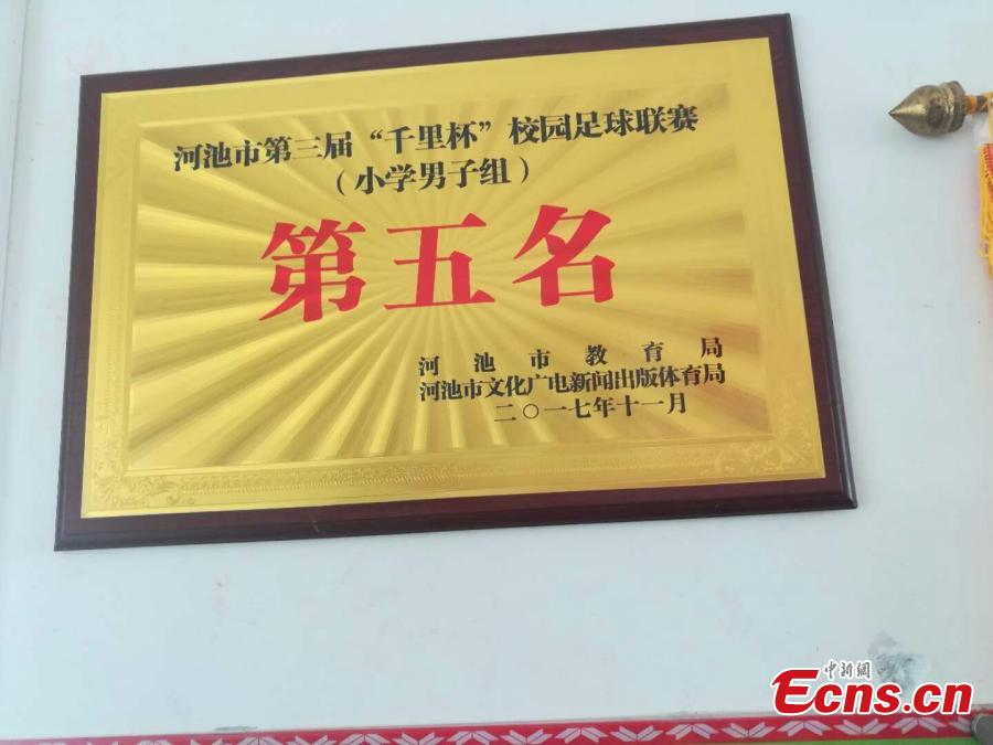 A certificate congratulates the Liuye Central Elementary School boys football team on their fifth placing in Hechi City, Guangxi Zhuang Autonomous Region in 2017. The mountainous county, with a population of 400,000 people, is one the poorest in the region. (Photo: China News Service/Jiang Xuelin)