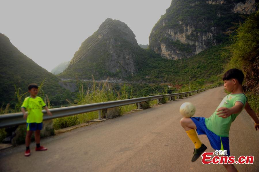 Wei Yuncheng plays football with Tang Qixing (R), whose father died and whose mother lives away for work. Tang also said his dream is to see the world beyond his high mountain home in Dahua Yao Autonomous County, South China's Guangxi Zhuang Autonomous Region. (Photo: China News Service/Jiang Xuelin)