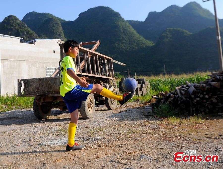 Wei Yuncheng plays football after school near his home in Liuye Township, Dahua Yao Autonomous County, South China's Guangxi Zhuang Autonomous Region. Wei, a member of the Liuye Central Elementary School boys football team, said his dream is to one day leave his mountain home to explore the outside world by playing football well. The mountainous county, with a population of 400,000 people, is one the poorest in the region. (Photo: China News Service/Jiang Xuelin)