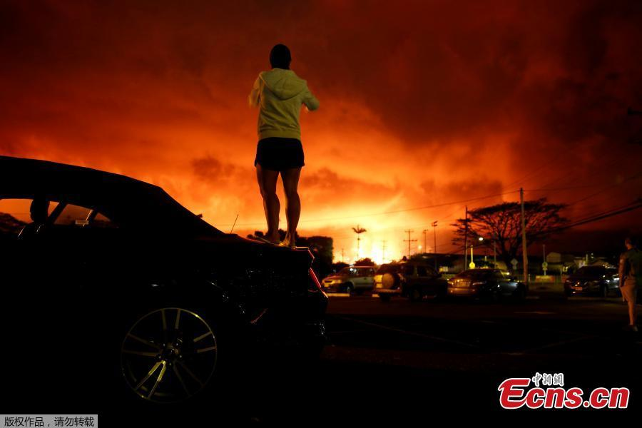 Lara Jackson, 34, of Manchester, Britain, takes a photo as lava lights up the sky above Pahoa during ongoing eruptions of the Kilauea Volcano in Hawaii, U.S., June 2, 2018. (Photo/Agencies)