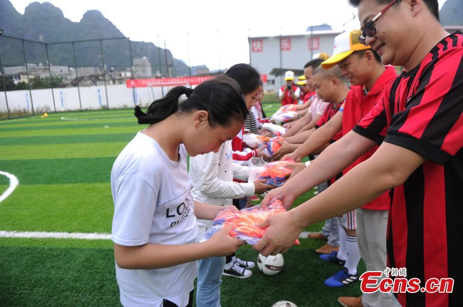 Volunteers from a road construction project donated football uniforms to Liuye Central Elementary School in Dahua Yao Autonomous County, South China's Guangxi Zhuang Autonomous Region. (Photo: China News Service/Jiang Xuelin)