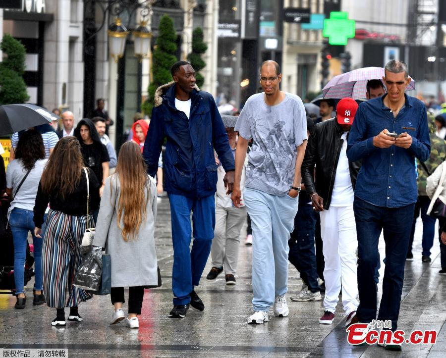 (L to R) Ivory Coast\'s Abdramane Dembele, 2m35, France\'s Brahim Takioullah, 2m46 and Armenia\'s Arshavir Grigoryan, 2m33, walk in the crowd on the Champs-Elysees Avenue in Paris, on June 1, 2018. A dozen of the world\'s tallest people met in Paris for a weekend. (Photo/Agencies)