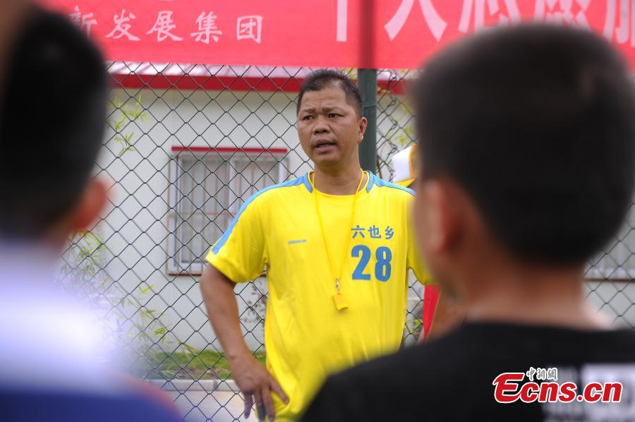 Lan Yushan, the coach of the Liuye Central Elementary School boys football team, has inspired children to develop an interest in football and dream big in Dahua Yao Autonomous County, South China's Guangxi Zhuang Autonomous Region. (Photo: China News Service/Jiang Xuelin)