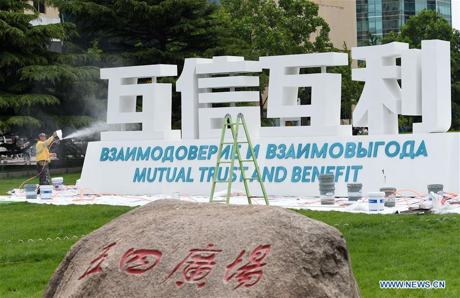 A staff member decorates a sign of Shanghai Cooperation Organization (SCO) Summit in Qingdao, east China\'s Shandong Province, June 2, 2018. The 18th SCO Summit is scheduled for June 9 to 10 in Qingdao. (Xinhua/Ma Ning)