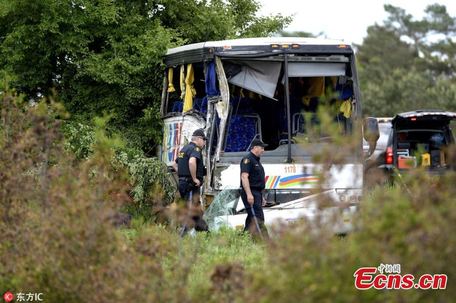 Ontario Provincial Police officers work at the site of a crash involving a tour bus on Highway 401 West, near Prescott, Ontario, Canada, June 4, 2018. At least 24 people are in hospital, four with life-threatening injuries, after a bus carrying 37 Chinese tourists crashed on the highway. A spokesman of the Chinese Embassy said that the embassy is in contact with the relevant Canadian authorities to verify the situation. (Photo/IC)