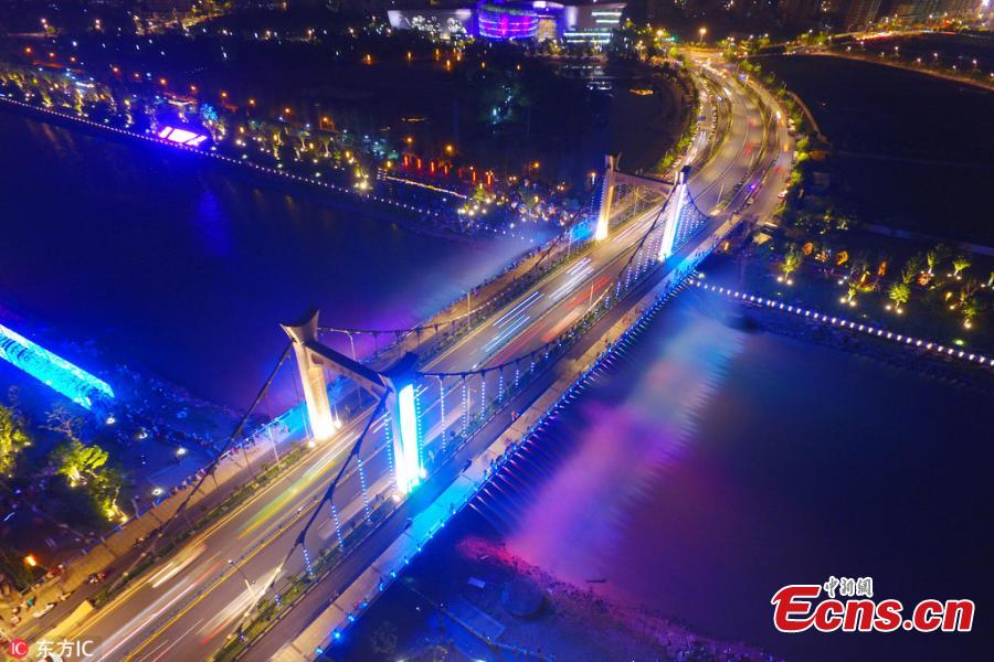 The Xiaolongwan suspension bridge is illuminated by a colorful lighting system in Jiangning District, Nanjing, Jiangsu Province, June 4, 2018. The 1,064-meter-long bridge has become a local attraction thanks to the amazing light show as well as a water spraying system operating from the bridge. (Photo/IC)